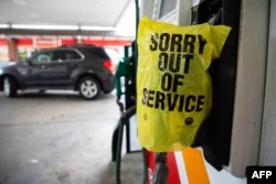 """FIE - An """"Out of Service"""" bag covers a gas pump as cars line up at a Circle K gas station near uptown Charlotte, North Carolina, May 11, 2021, following a ransomware attack that shut down the Colonial Pipeline, a major East Coast gasoline transporter."""