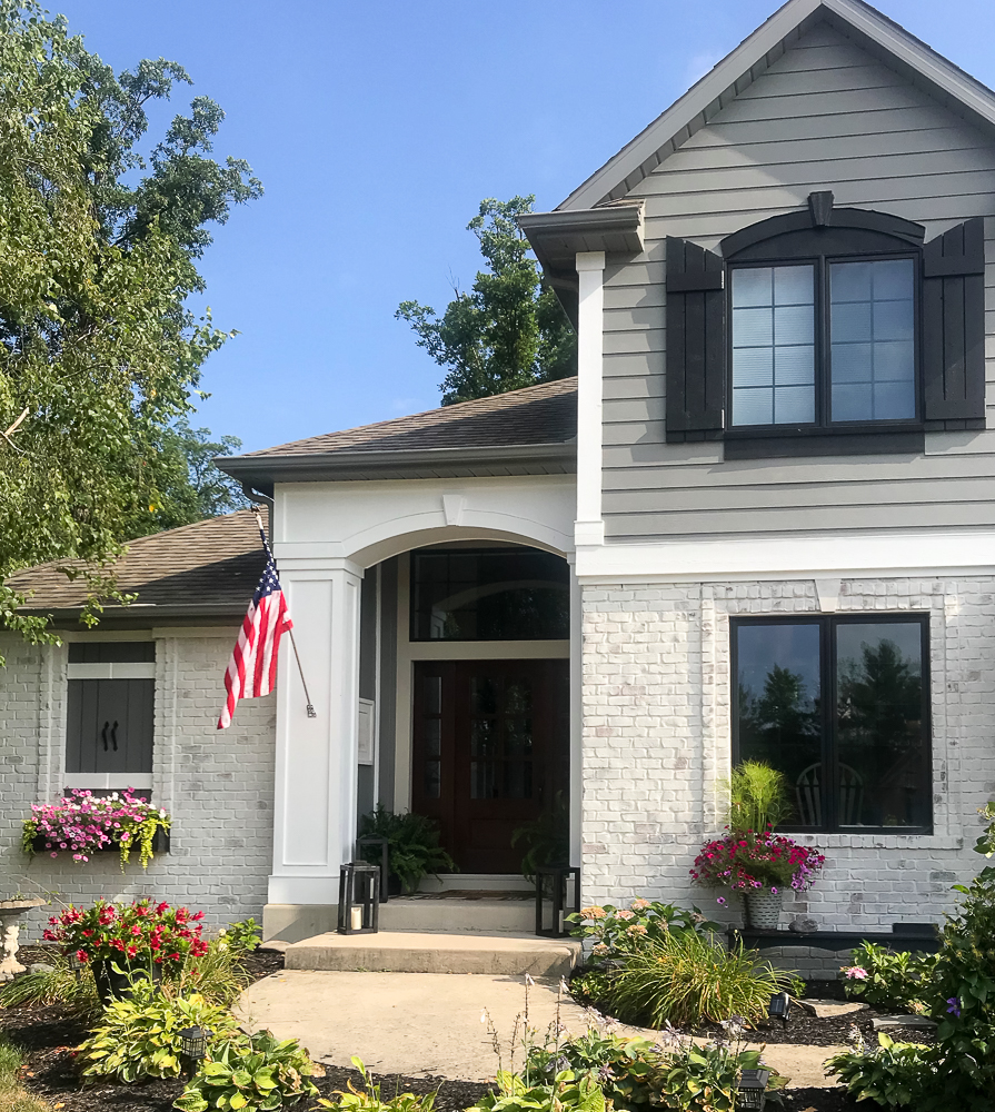 Craftsman home with American Flag and lots of pink flowers and great exterior paint colors