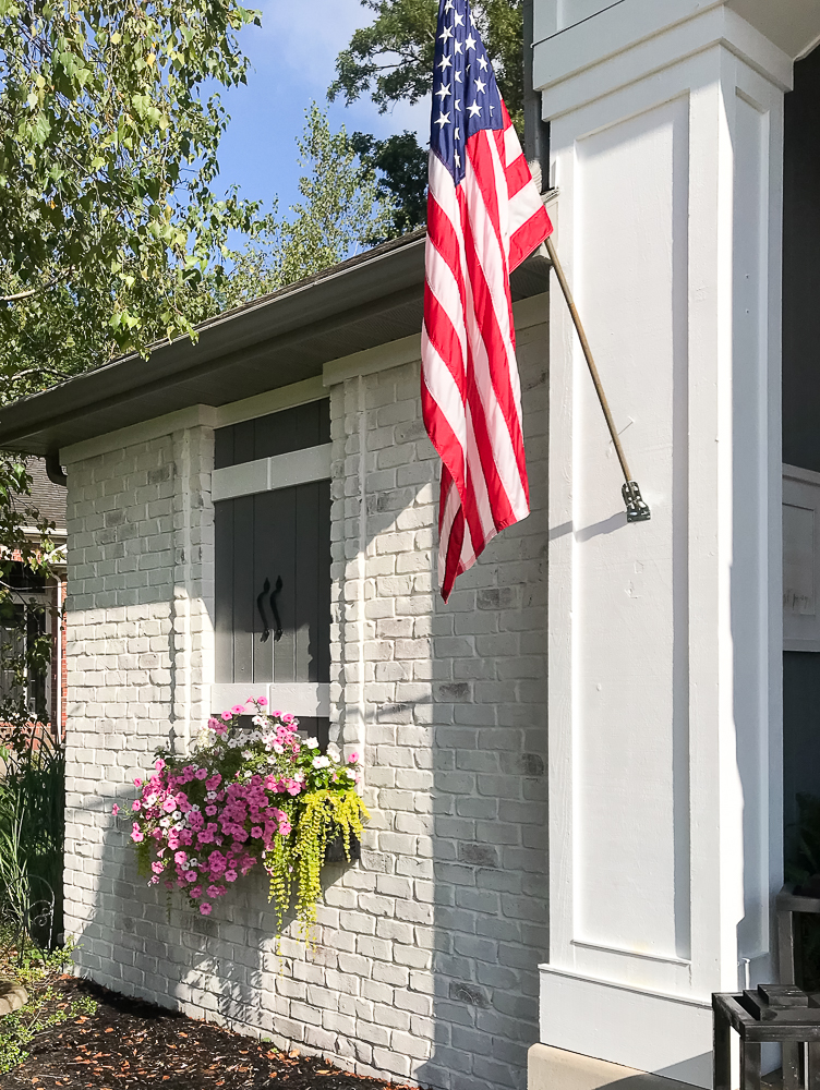 American Flag, flower box with pink flowers, Faux window, limewashed brick