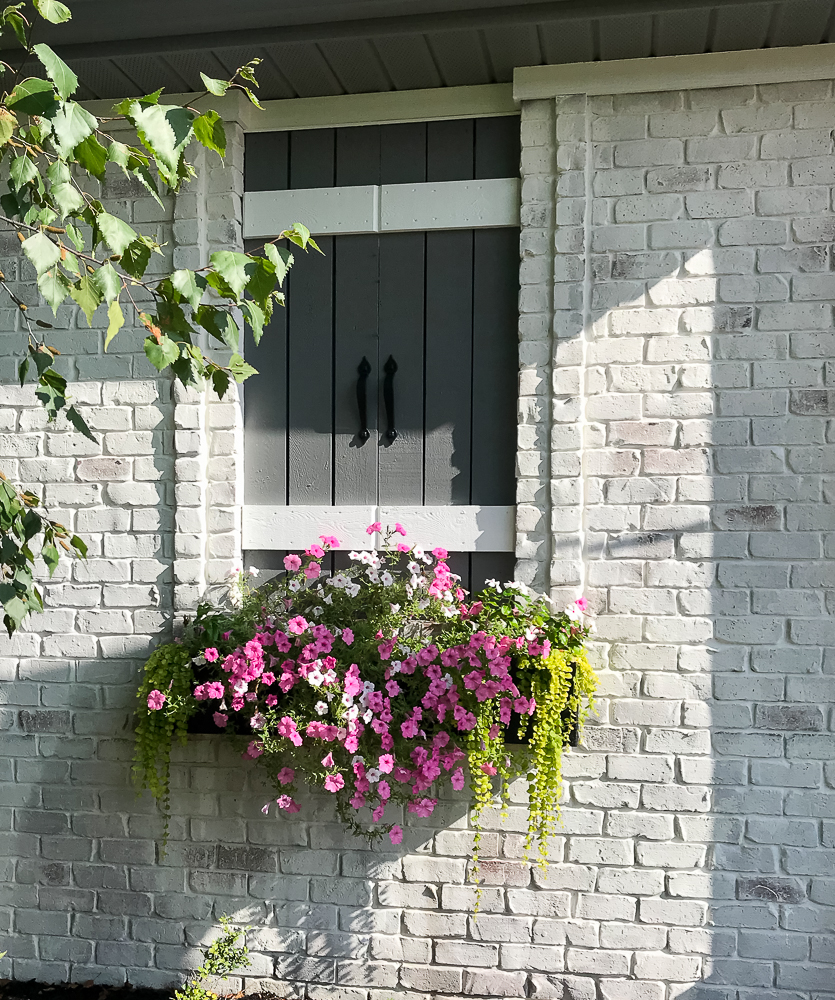faux window with flower box and full pink flowers