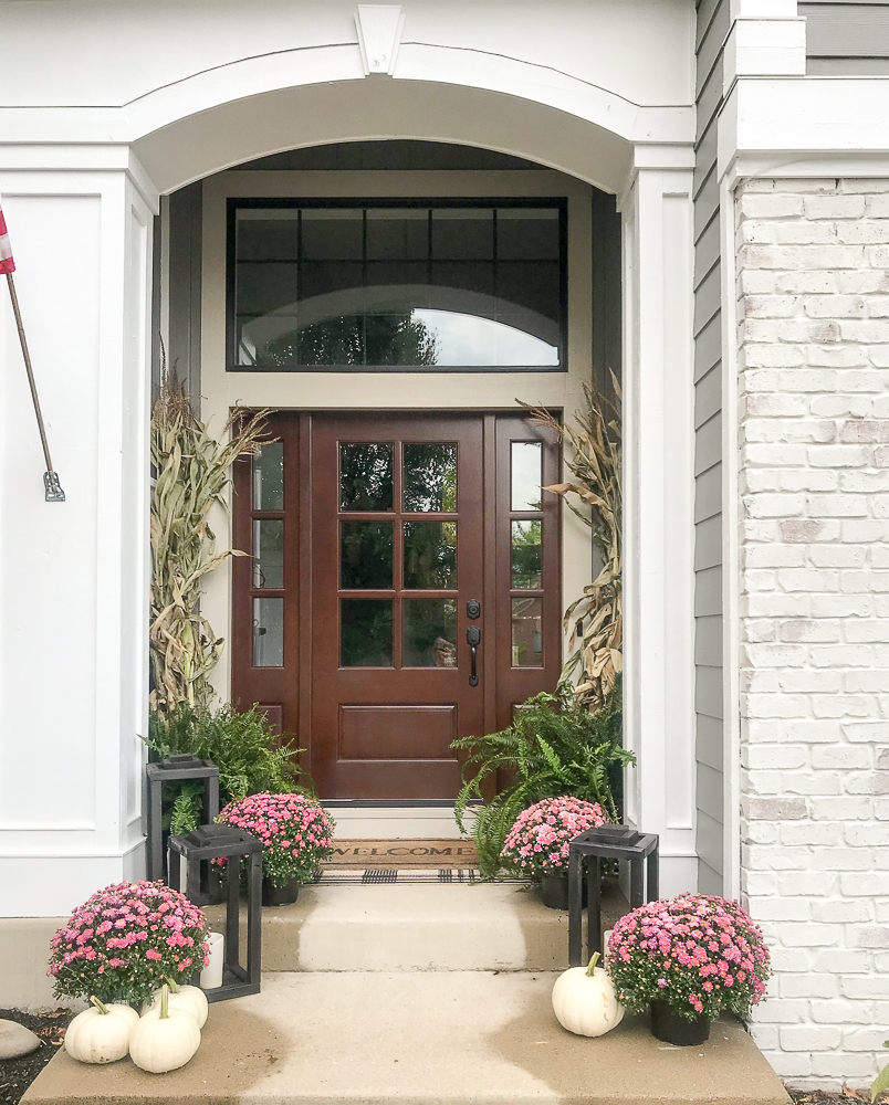 a new front door with mums adds curb appeal