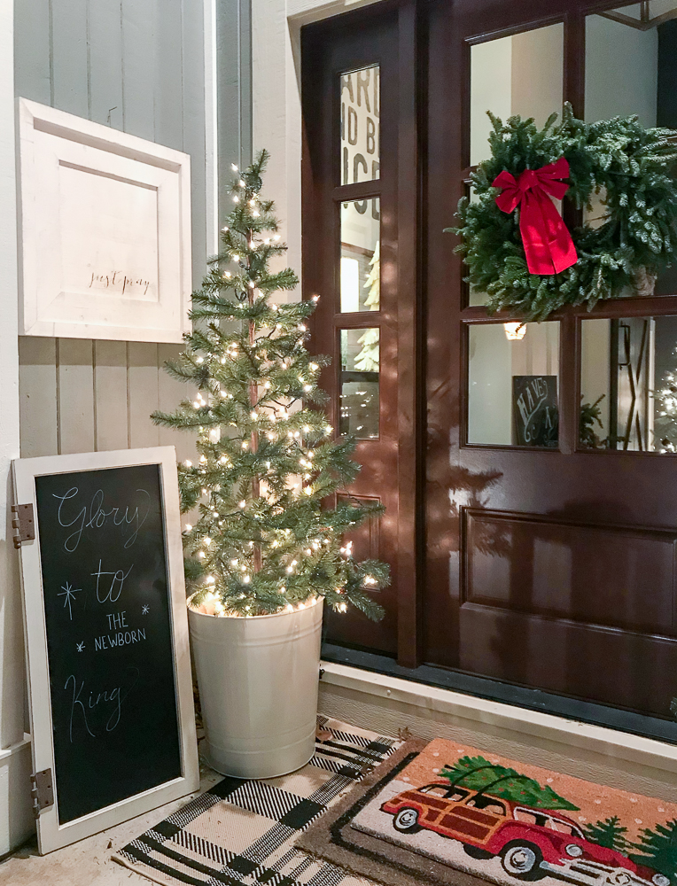 front porch with christmas tree, rug and sign