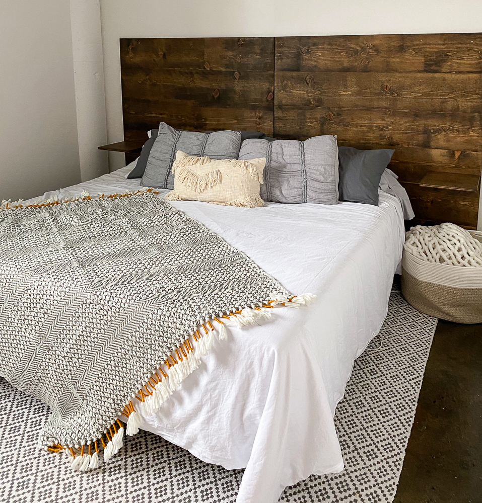 boho style bedding on king bed with wooden headboard