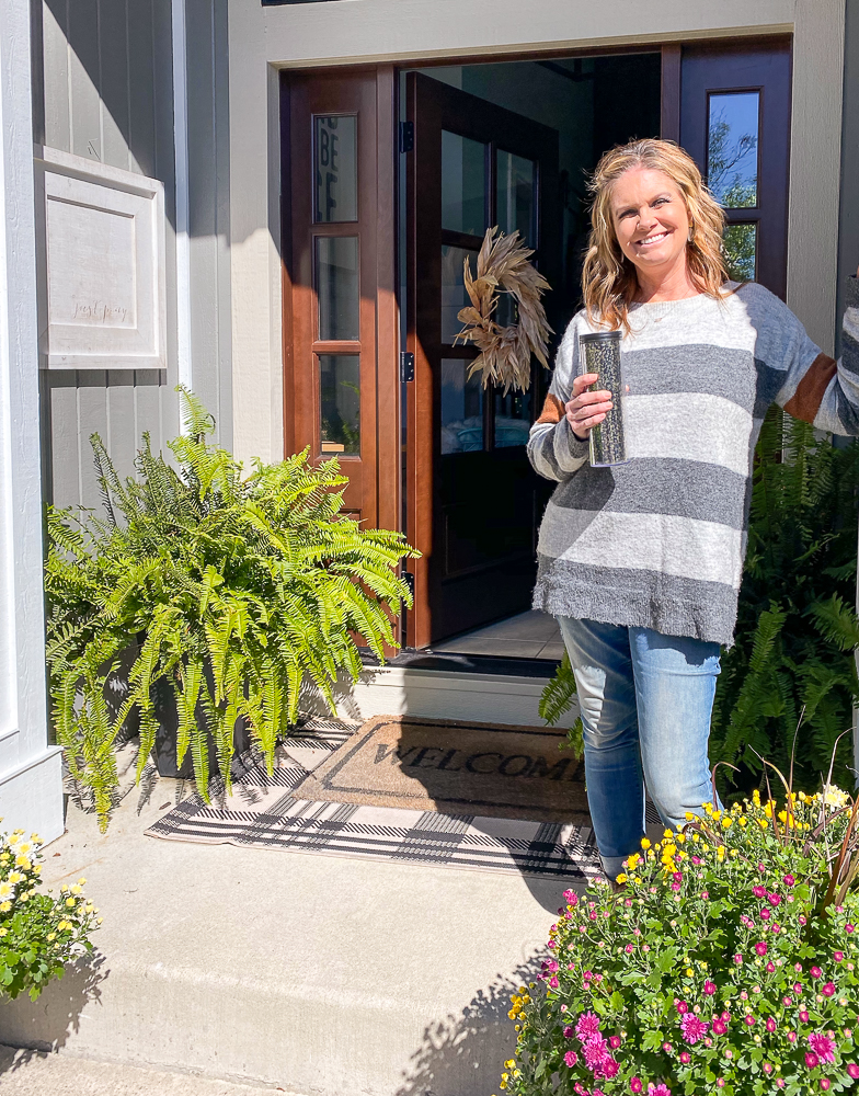 Girl standing on front porch with a hot drink and a fern behind her