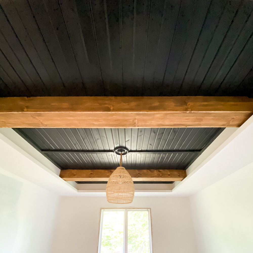 black planked ceiling with stained faux beams
