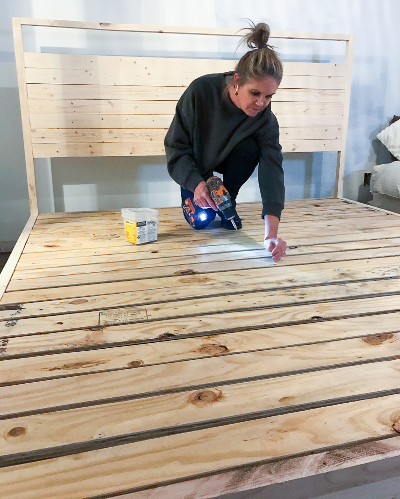Girl attaching screws to supports for platform bed frame