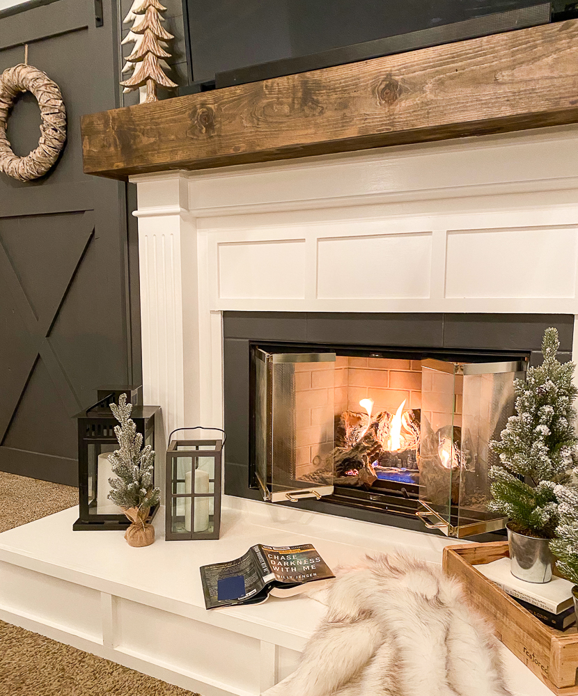 Cozy fireplace with fuzzy blanket and a book