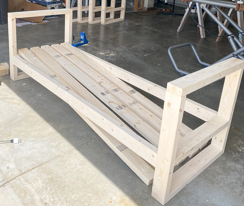 2x4's cut to fit between armrests to form seat for outdoor sofa