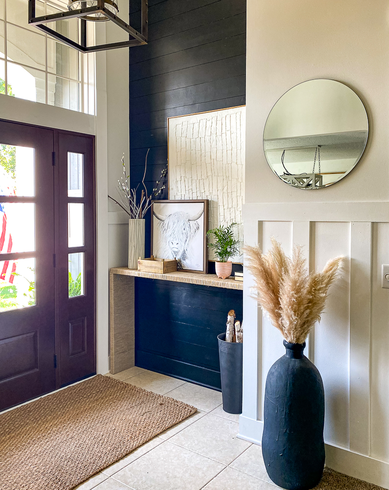 Foyer space with big open windows front door and beautiful decor
