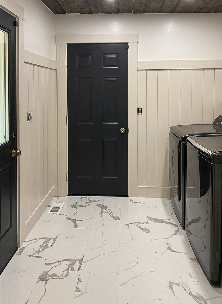 Laundry room with black doors and tile floors