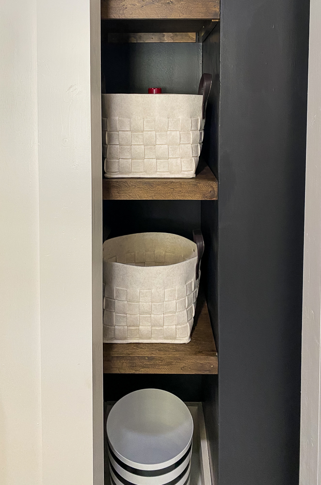 Open shelving in a cubbie space with black walls and white baskets