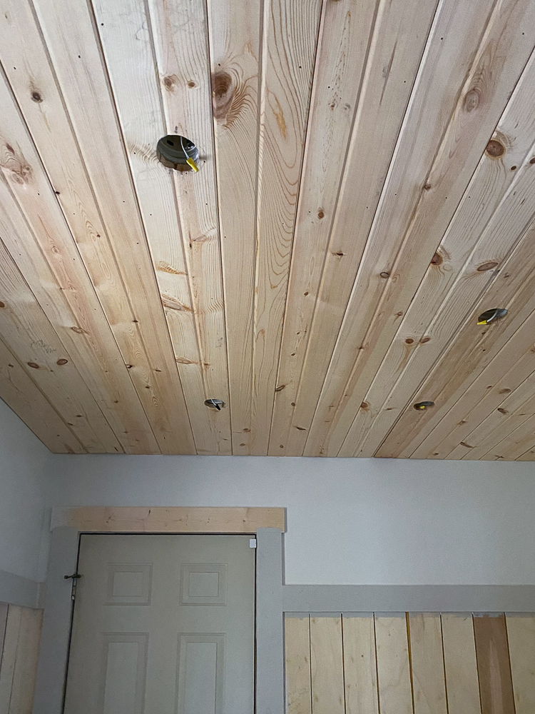 Carsiding ceiling with white walls and putty colored trim in a laundry room