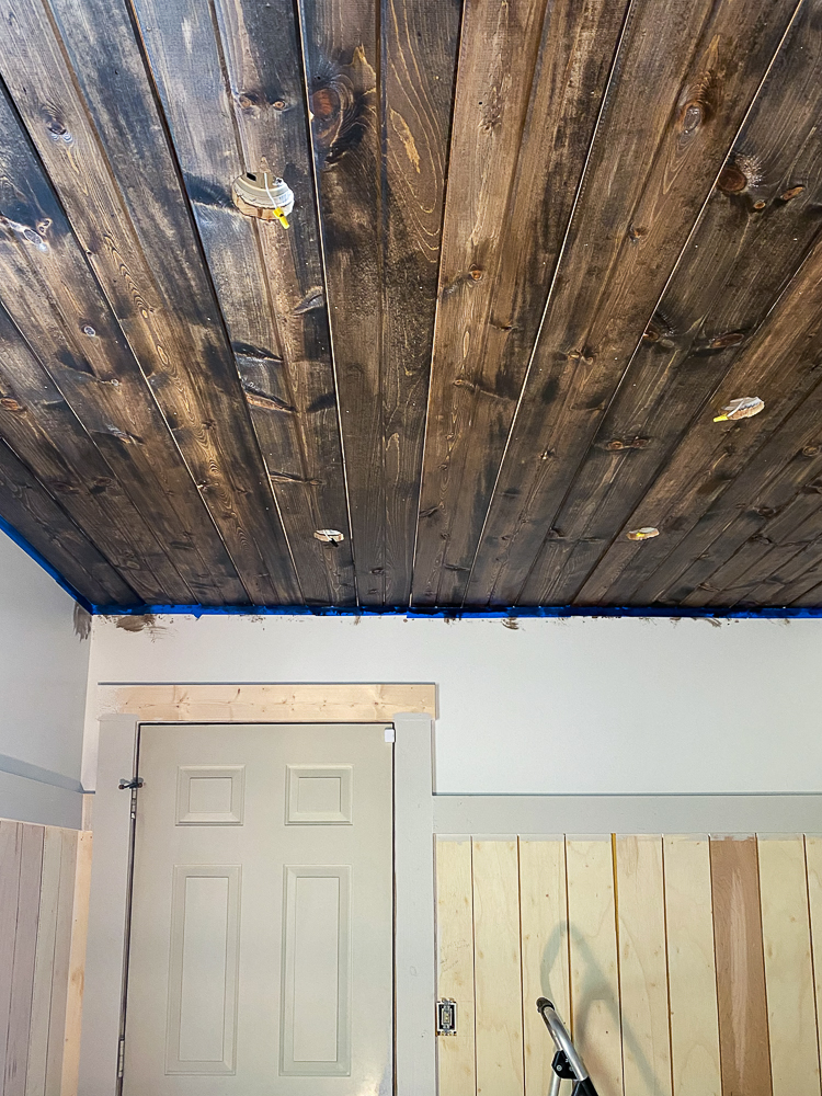Stained carsiding ceiling with white walls and vertical shiplap
