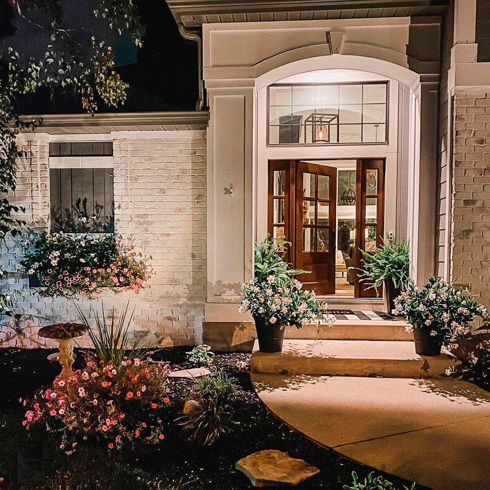 Night scene of the front of a house with door partially open and spotlights shining on house