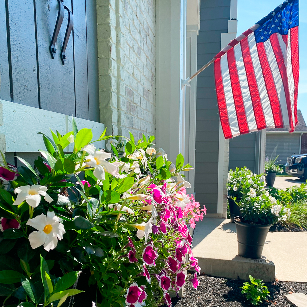 Window box with flowers and an American flag for outdoor fall decorating