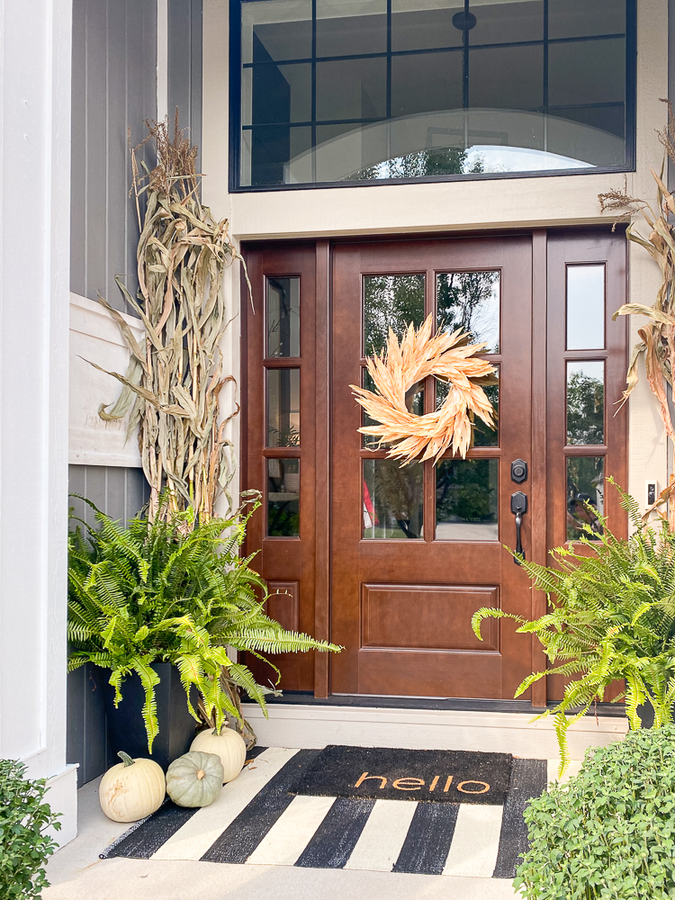 Outdoor fall decorating on a front porch with wooden door with windows and sidelights