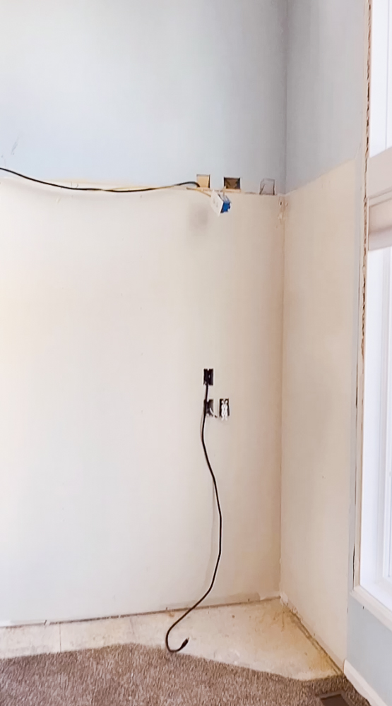 Empty wall space with a cord hanging down.