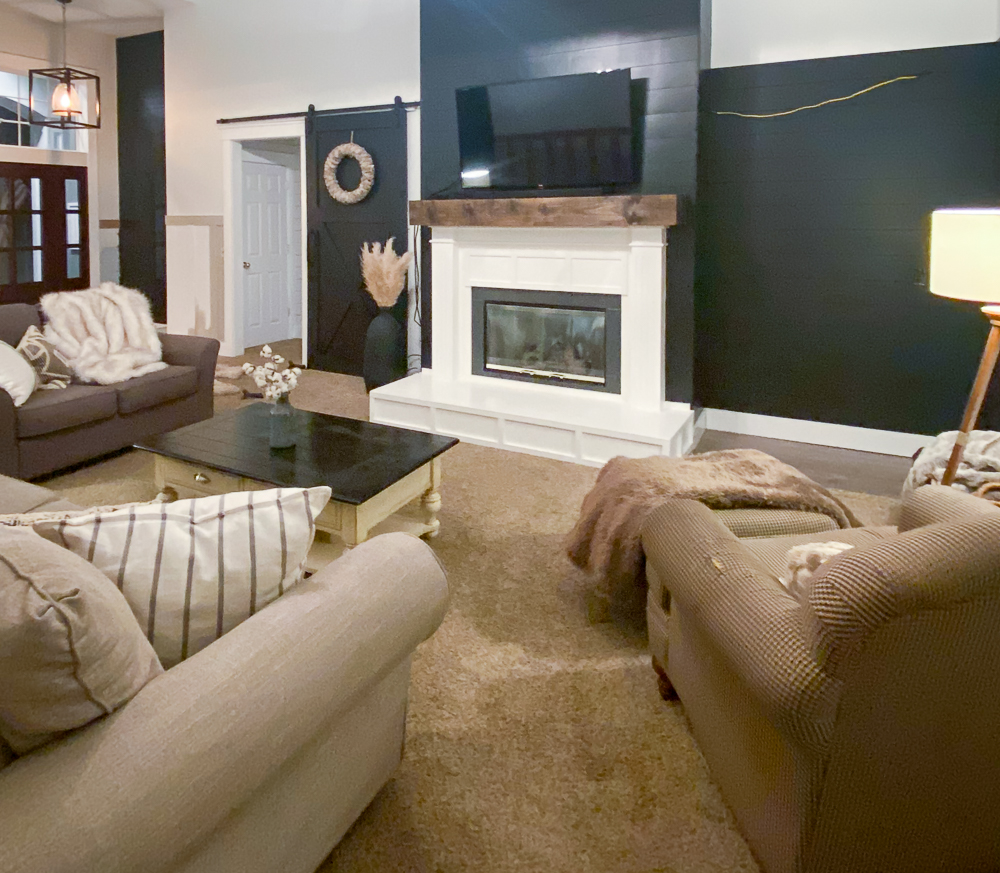 Family room with black shiplap walls and a large sliding barn door