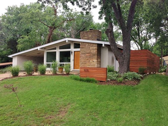 mid century modern house exterior view with stone chimney