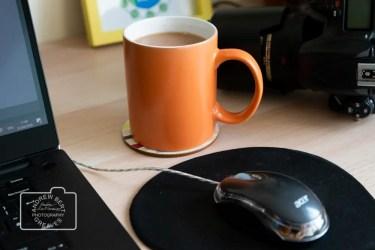 A mug of tea, laptop and a DSLR camera