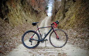 A gravel bike on a dirt road with high canyon walls