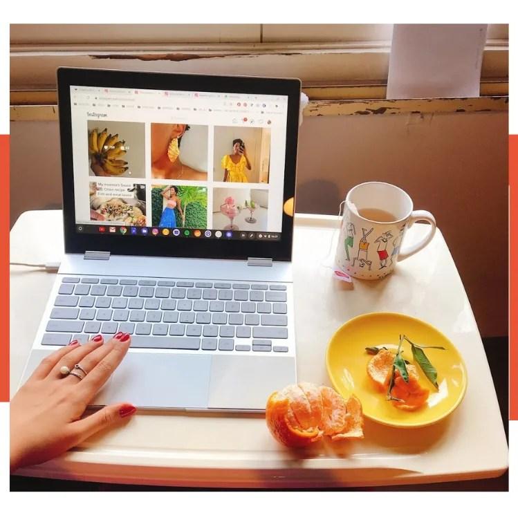 Foto com uma borda branca e laranja. A foto é composto por uma mesa branca com um notebook cinza ao centro com um instagram aberto, caneca de chá ao lado, um prato amarelo com tangerina descascada e mão com unhas vermelhas usando o mousepad.