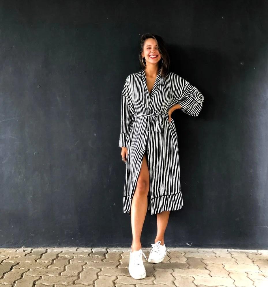 Garota posando em uma parede preta com um quimono mídi listrado em preto e branco com amarração na cintura usado como vestido. O look ainda conta com tênis branco e brincos de argola prateado.