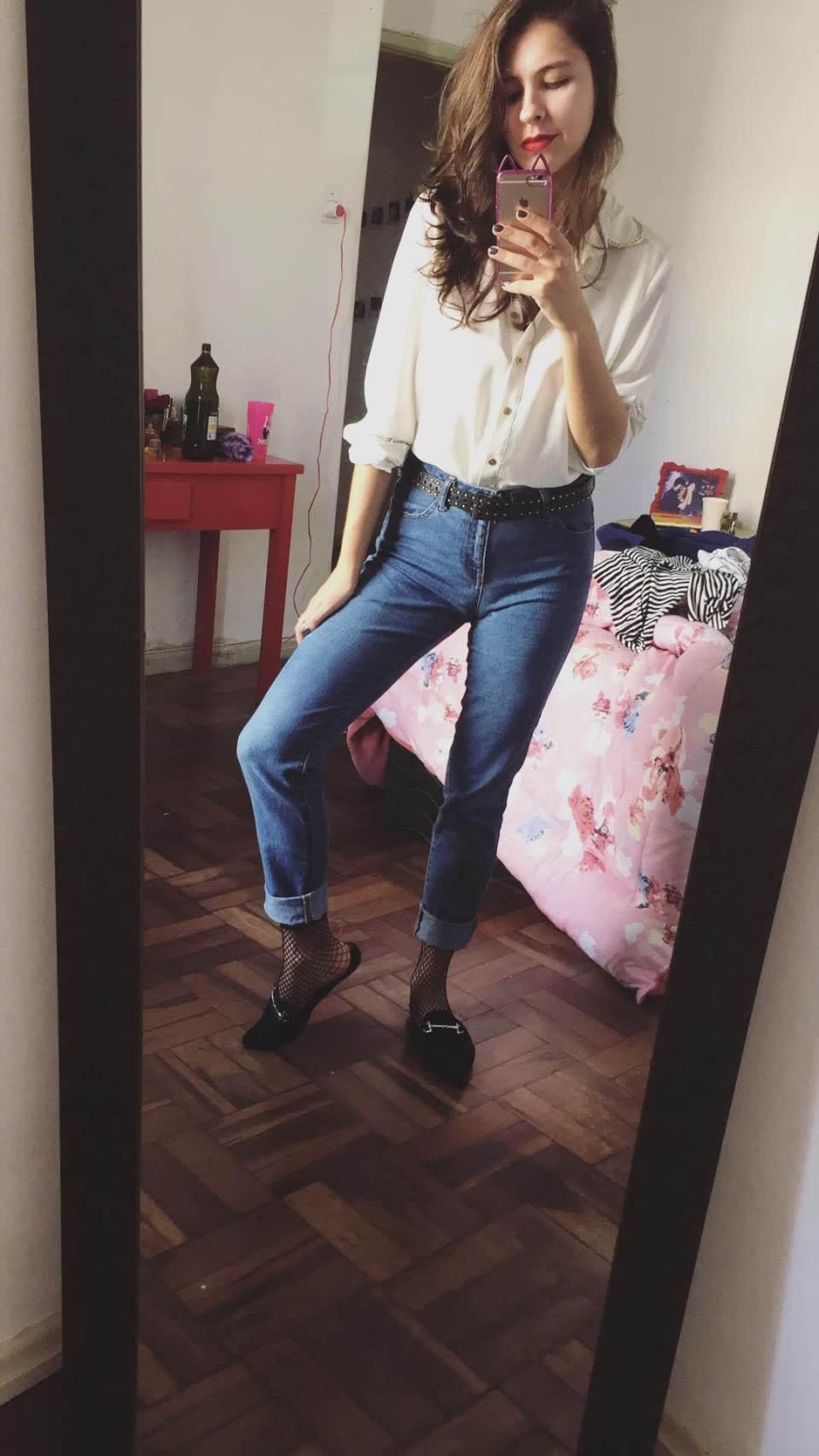 Marcie posa em frente a um espelho, com o celular no alto tirando a foto. O look é composto por camisa branca para dentro da calça jeans, cinto preto com tachas, mule preto e meia arrastão.