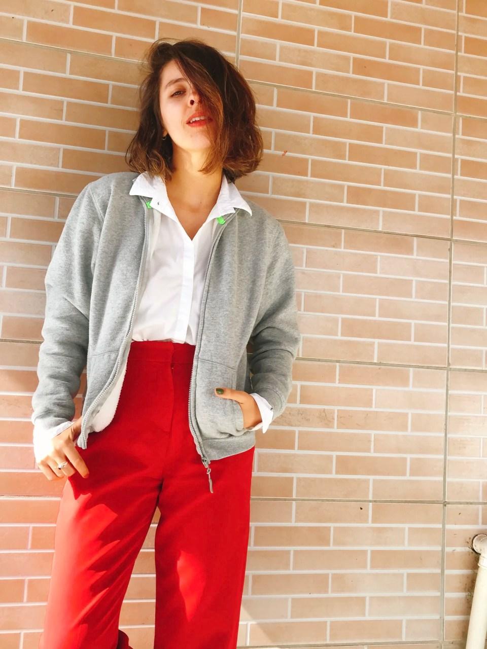 Marcie posa em frente a uma parede de tijolos laranja, a foto tirada do joelho para cima. O look é composto por camisa branca usada para dentro da calça de alfaiataria vermelha e jaqueta bomber de moletom cinza.