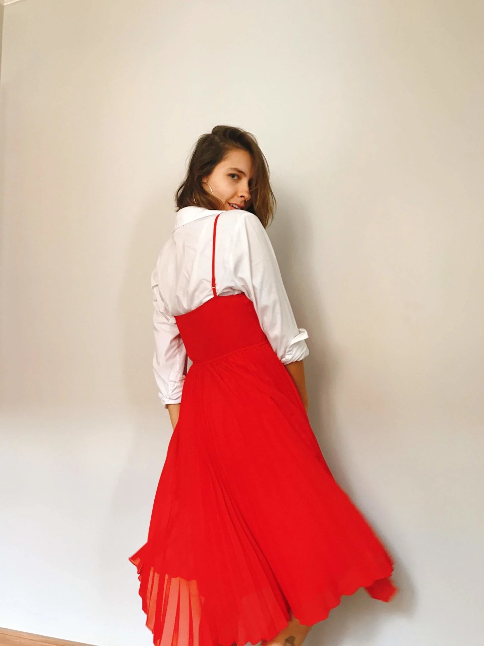 Marcie posa em frente de uma parede branca, de costas, olhando por cima do ombro. O look é composto por camisa branca, usada por baixo de um vestido vermelho plissado de tiras finas mídi.