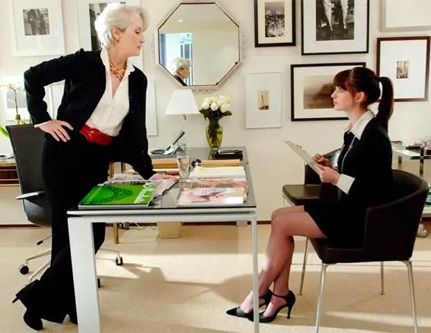 """Foto de cena do filme """"O diabo veste prada"""". Miranda está de pé de terno preto, camisa branca e cinto vermelho está olhando para a Andrea, que está sentada com um vestido preto, scarpin preto e camisa branca."""