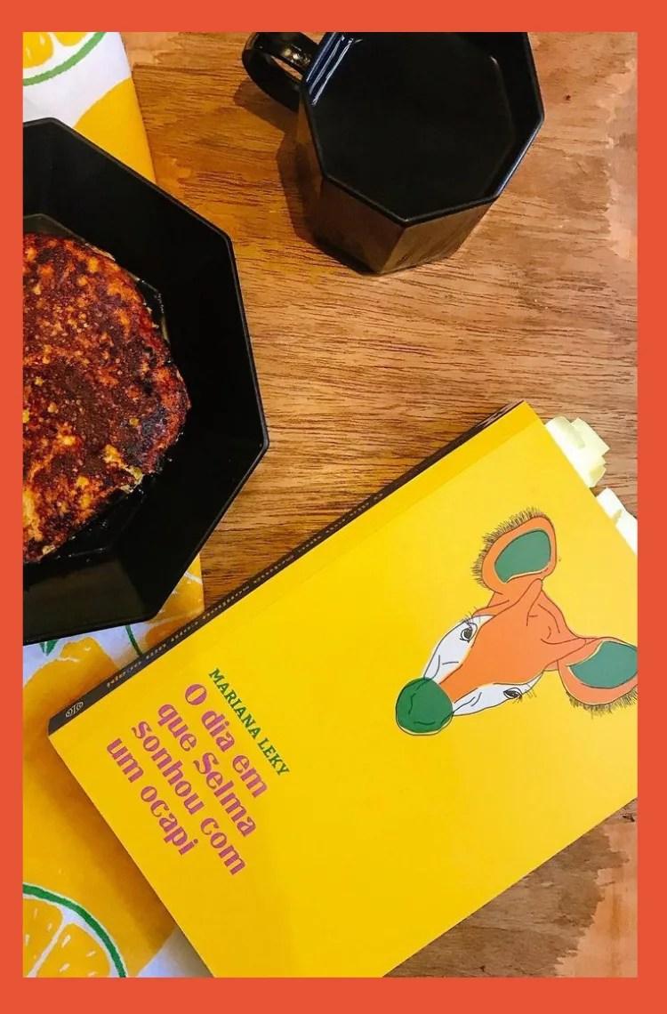 """Foto vertical com borda laranja. Em cima da mesa marrom de madeira está uma caneca preta com café, uma panqueca em um prato preto e um livro com capa amarela, uma cabeça de animal ilustrada e o título """"O dia em que Selma sonhou com um Ocapi"""" em rosa."""