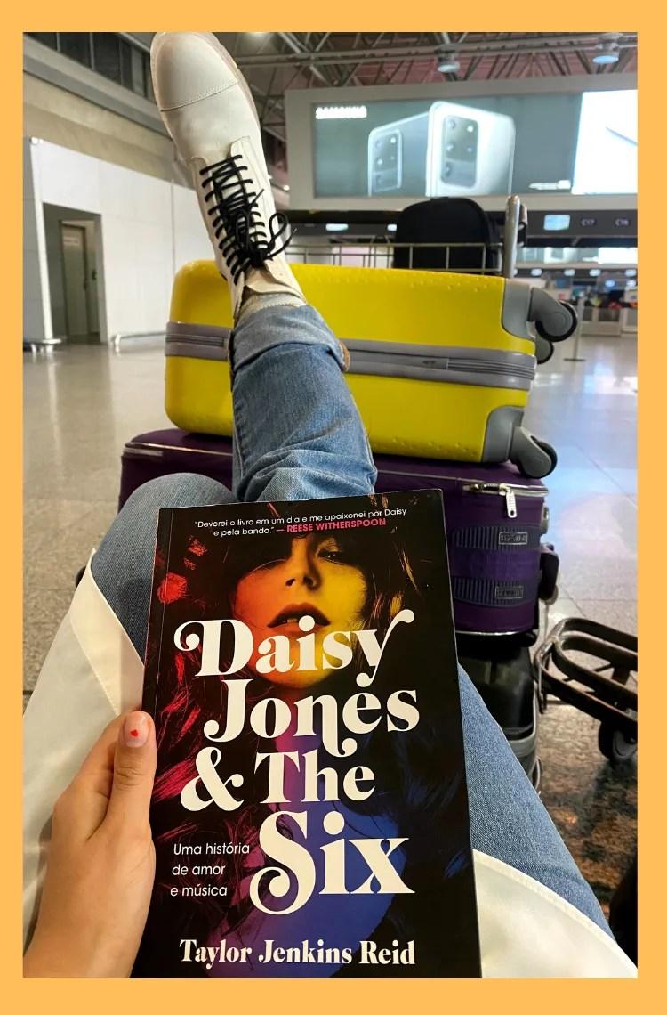 Foto vertical com fundo amarelo. Na foto, está o Daisy Jones & the six no colo, com calça jeans e coturno branco, escorado nas malas.