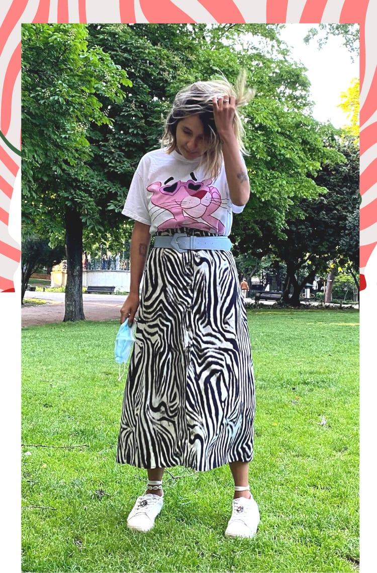 Foto com borda branca, mostrando uma forma de usar saia de zebra em looks. O look é composto por saia de zebra mídi com botões frontais, camiseta branca com estampa pantera cor de rosa, cinto azul claro e tênis branco.