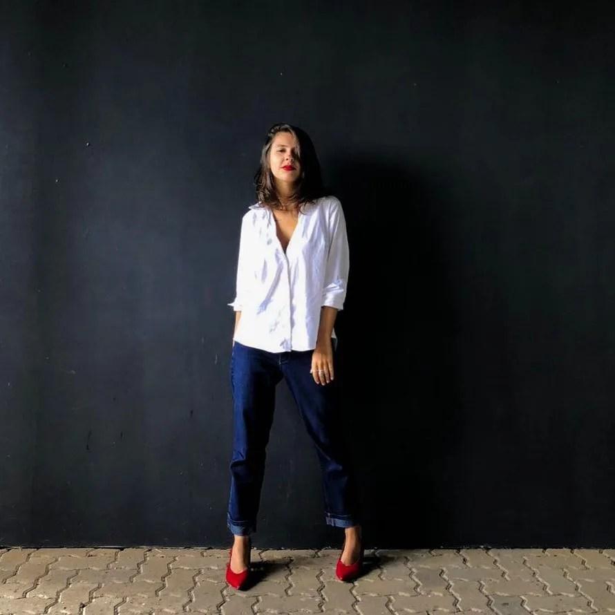 Marcie posa em frente a uma parede preta olhando para a câmera. O look é composto por camisa branca solta, calça de alfaiataria boyfriend com barra dobrada e scarpin vermelho.