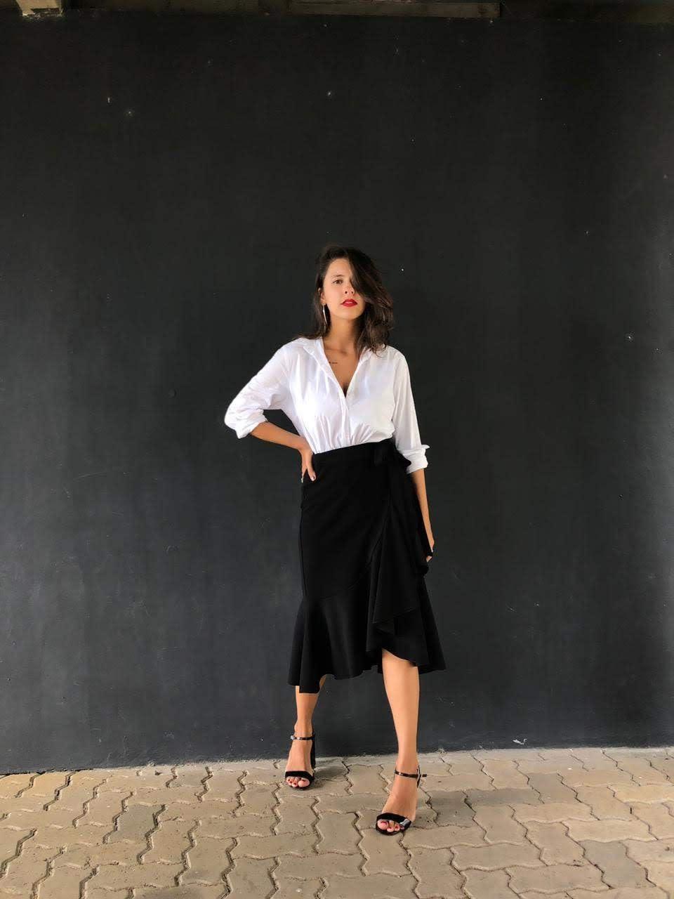Marcie posa em frente a uma parede preta, com a mão na cintura. O look é composto por camisa branca, saia de babados preta mídi e sandália preta de tiras finas.