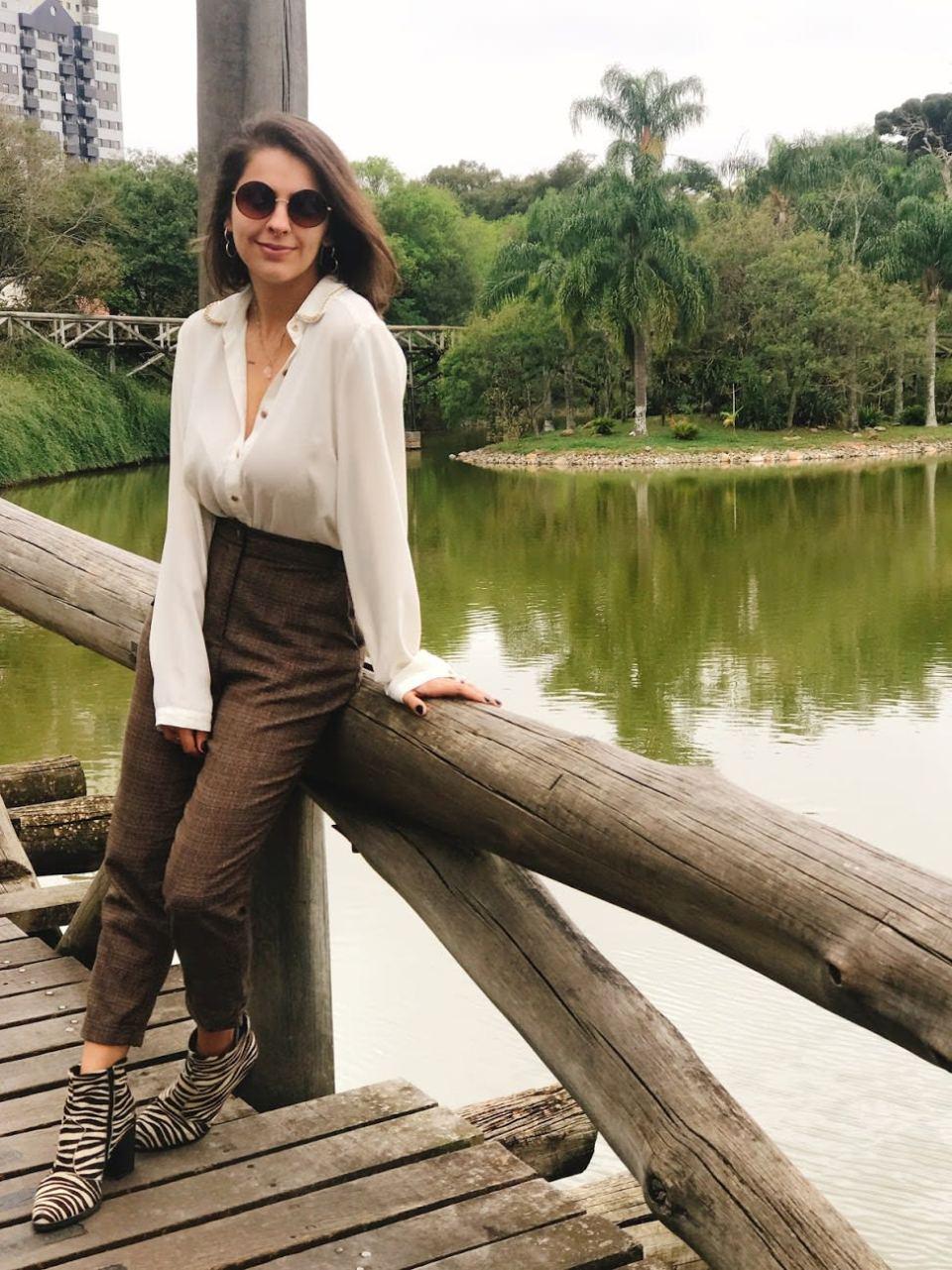 Marcie posa em frente a um lago e árvores. O look é composto por camisa branca com botões dourados e gola de corrente, calça de alfaiataria marrom xadrez e bota animal print de zebra.