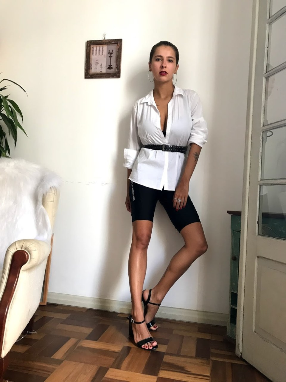 Marcie posa em frente a uma parede branca, com uma poltrona branca ao lado. O look é composto por camisa branca com decote profundo, cinto preto com tachas, bermuda ciclista preta e sandália preta de tiras finas.