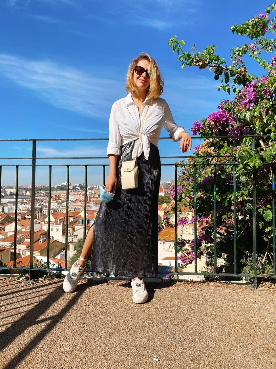 Marcie posa em frente a um miradouro, com céu azul e mini casas ao fundo. O look é composto por camisa branca amarrada na cintura, saia longa prateada, bolsa branca a tiracolo e tênis branco com cadarços amarrados na canela.