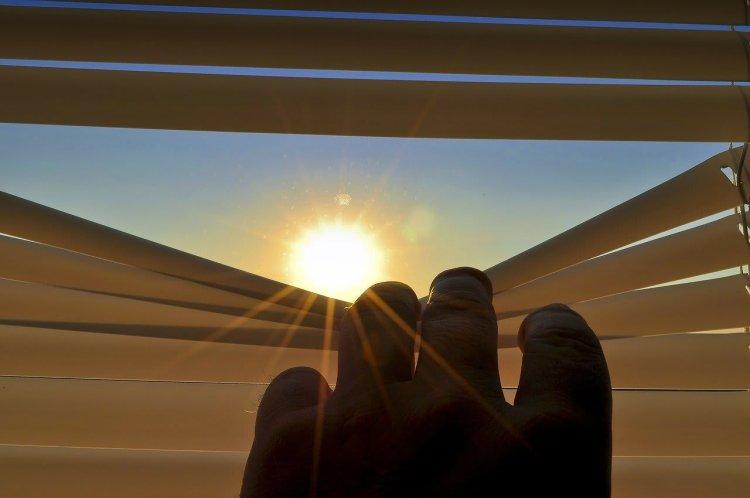 Persona al interior de su casa, observando el sol desde unas persianas.