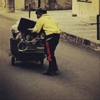 Copilaș împingând la un căruț plin cu materiale reciclabile