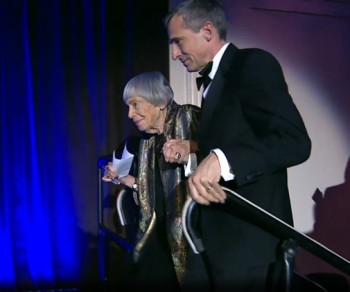 Theo Downes-Le Guin escorts his mother, Ursula Le Guin, on stage