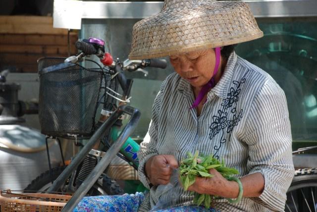 Cette femme prépare des bouquets de fleurs pour les touristes.