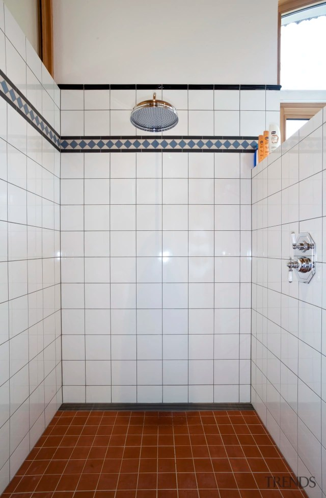 shower with brown tiles on floors a