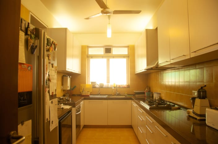 U Shaped Modular Kitchen With White Glossy Cabinets And