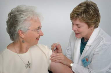 A nurse giving a middle-aged woman a vaccination shot : Free Stock Photo