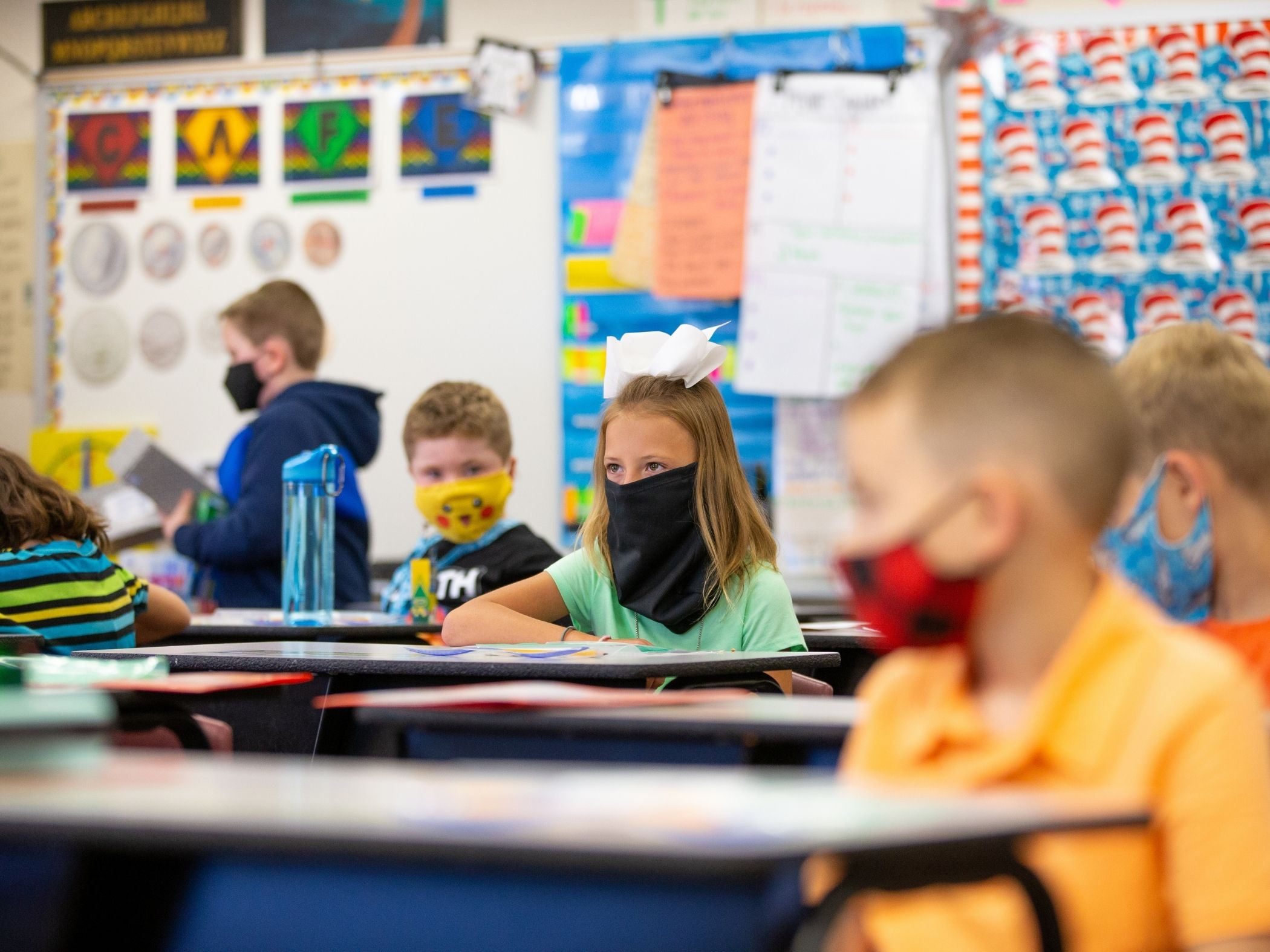 Students in class sitting at desks with masks on
