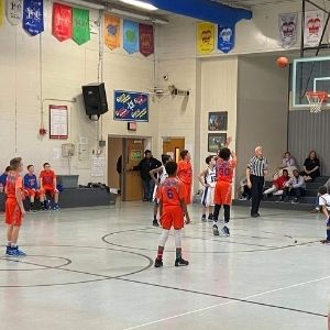 Boy shooting free throw while teammates, opposing team, umpires and fans watch