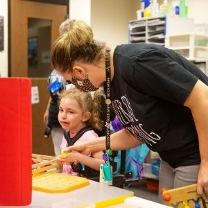 Teacher assists student in hands-on activity