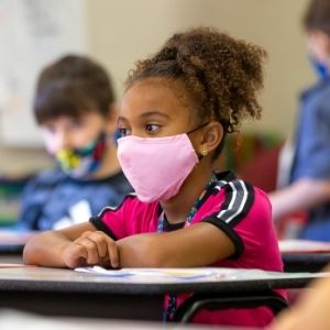 Young girl student with mask at her desk coloring